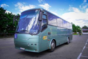 zielony autobus nauki jazdy na parkingu